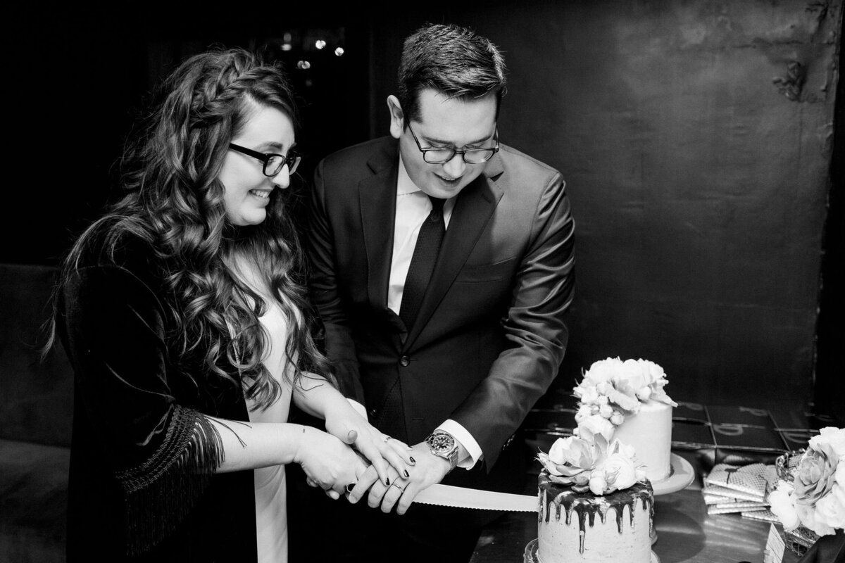 Wedding couple cutting cake black and white