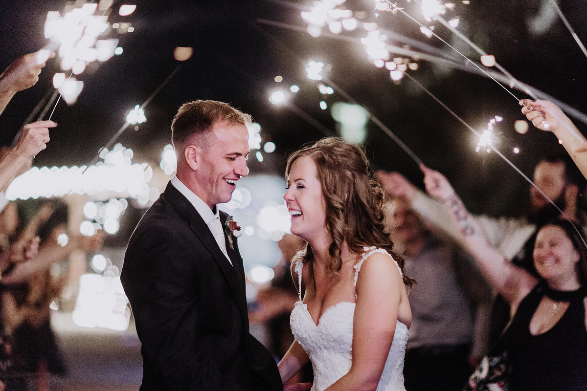 reno wedding photographers bride and groom under sparklers laughing