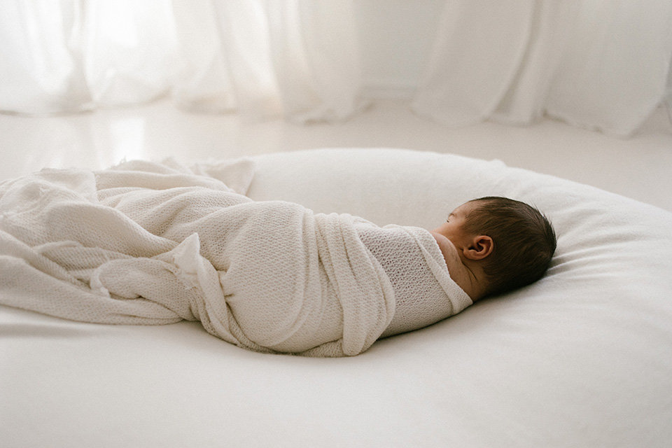newborn baby laying on a white blanket during natural and unposed newborn session