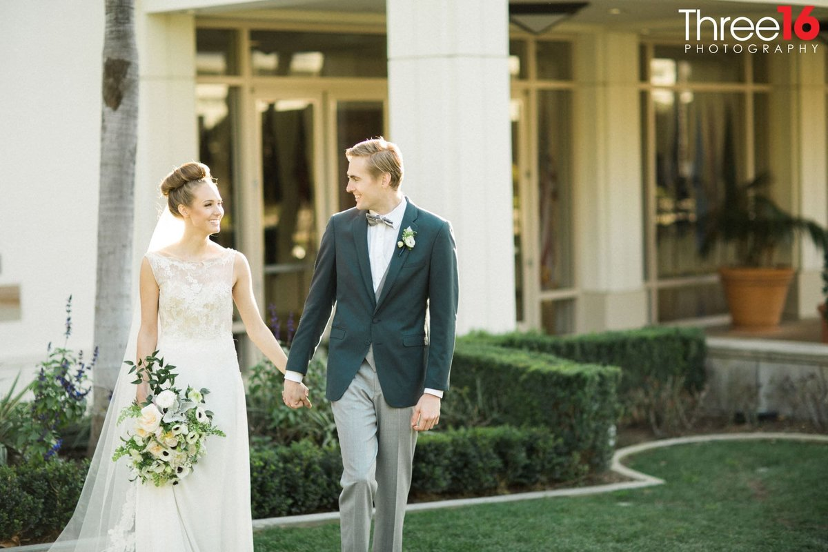 Bride and Groom walk hand in hand at the Richard Nixon Library wedding venue
