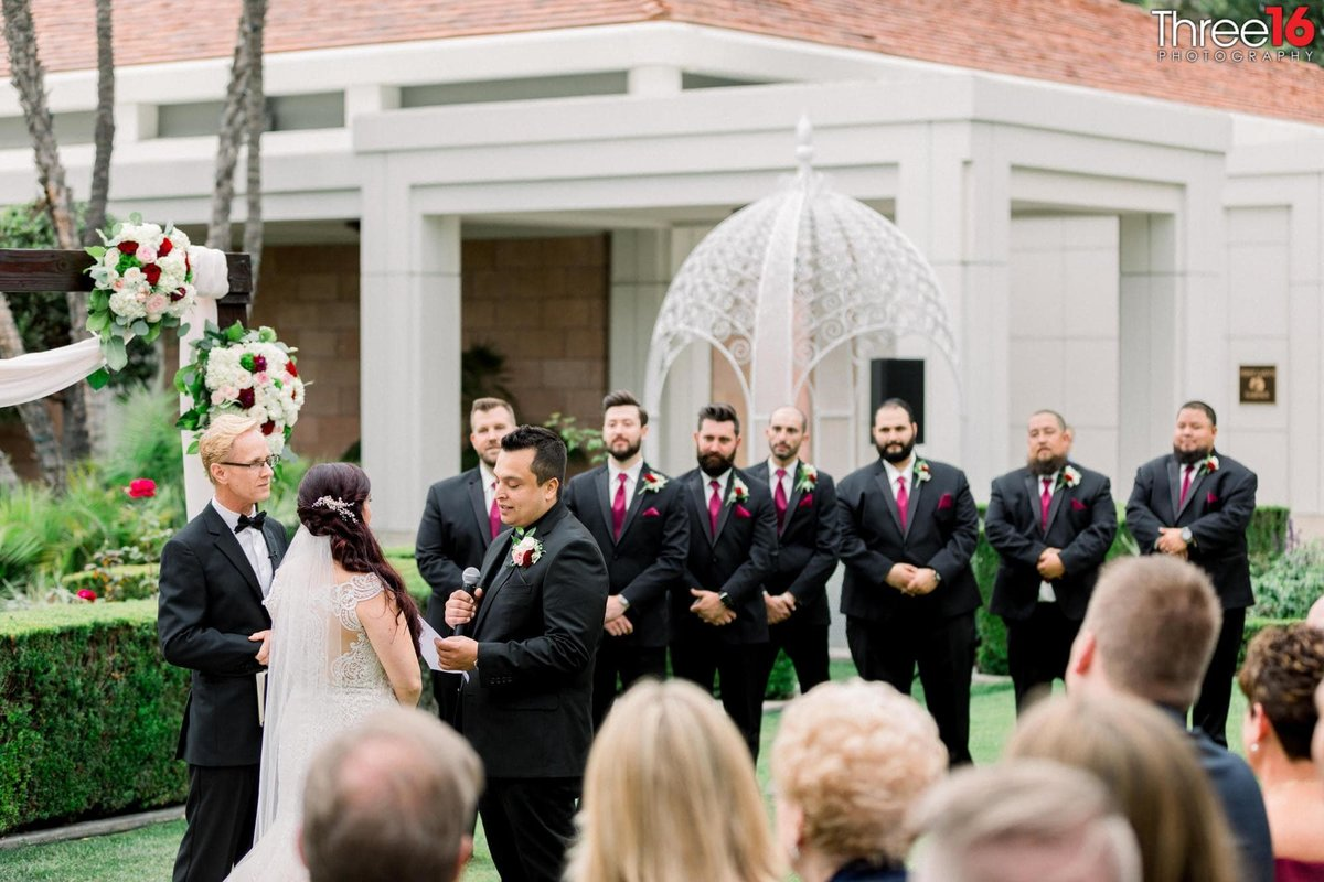 Groom reads his vows to his Bride as the Groomsmen watch