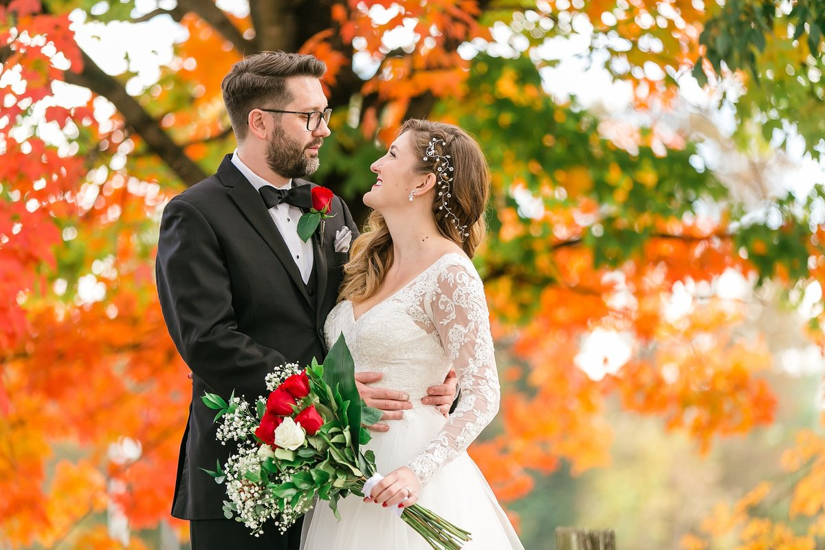bride-groom-embrace-fall-leaves