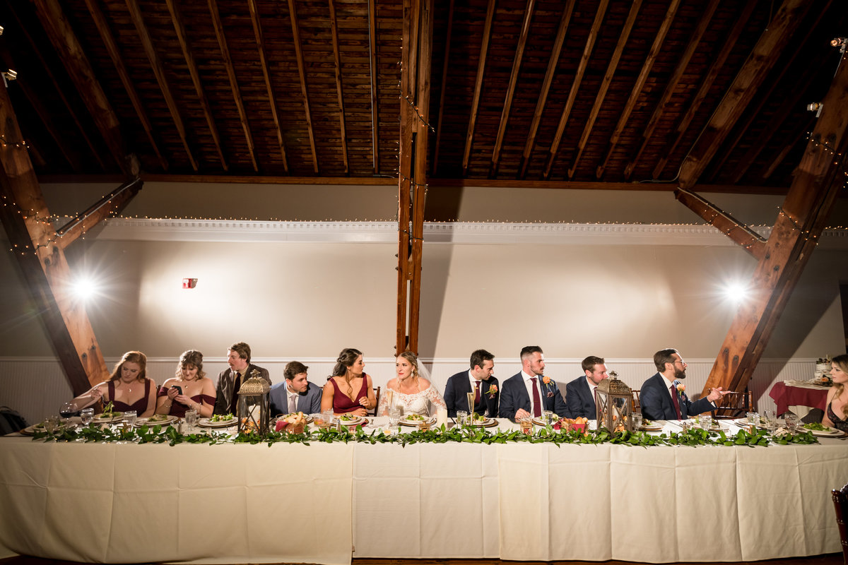 wedding party at head table during reception barn wedding venue nh