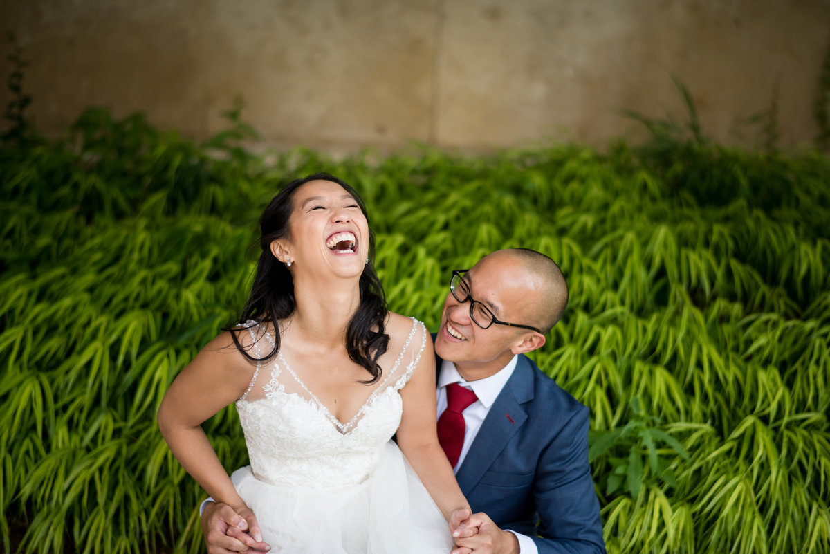 Bride laughing while sitting on groom's lap