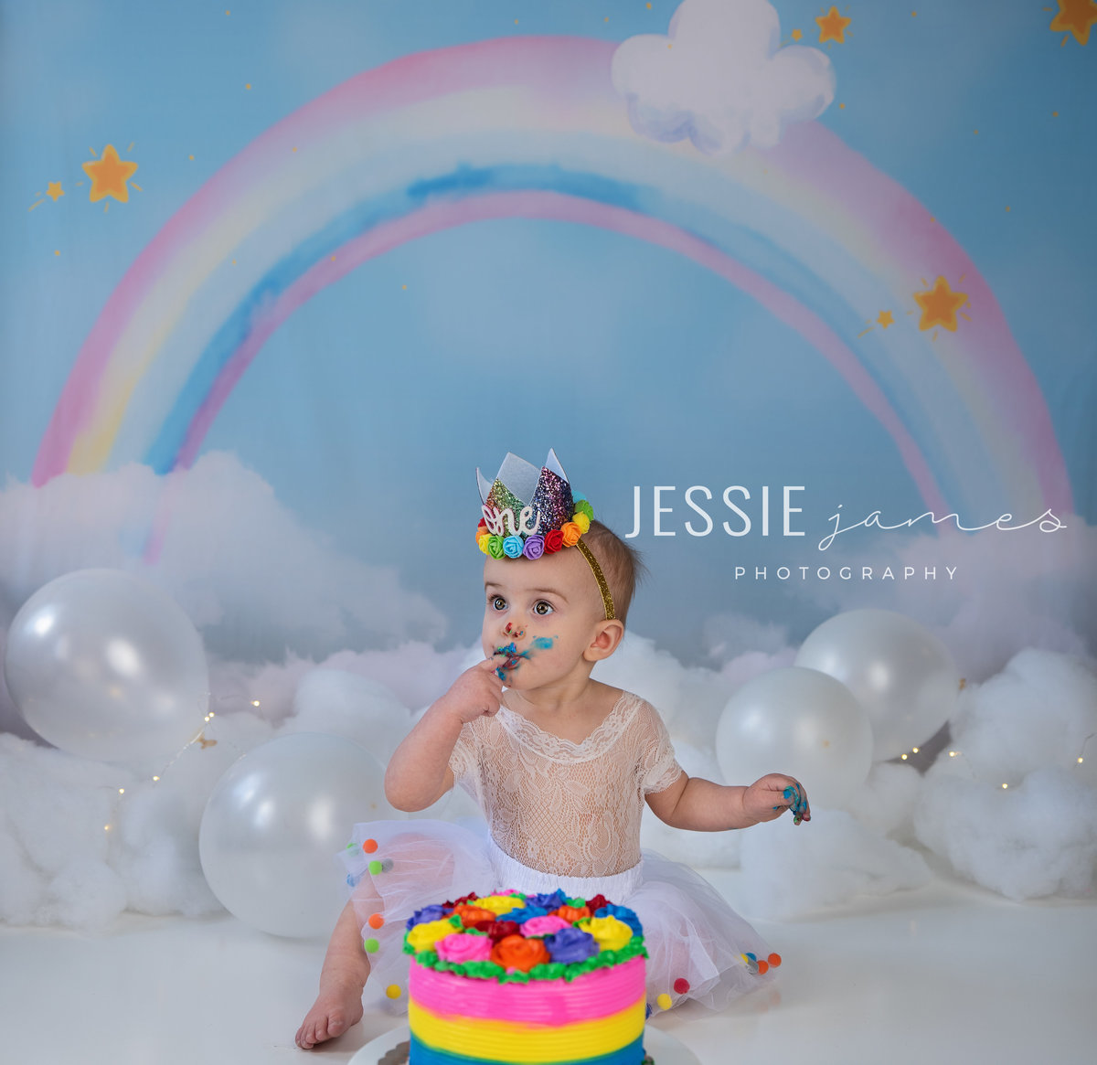 one year old girl eating cake in front of a rainbow backdrop