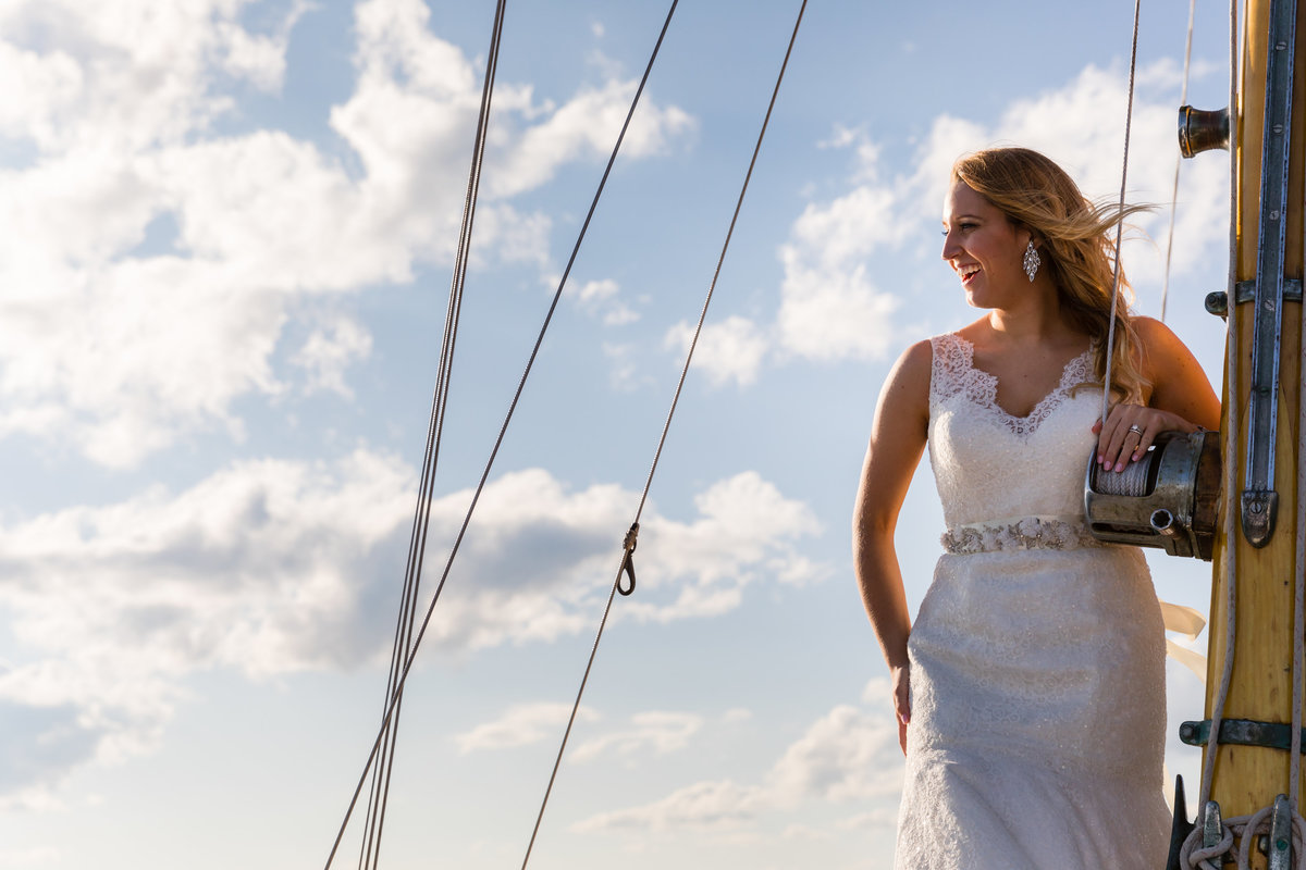The bride stands tall with the mast on the Silverlining Sailboat in Ogunquit Maine