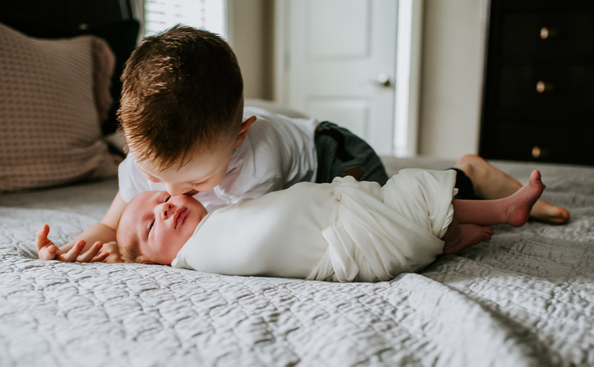 big brother kissing new baby brother