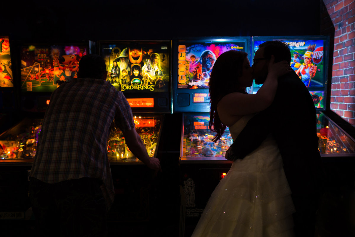 Portland Maine Wedding Photographer the bride and groom kiss in front of the arcade games on their wedding day