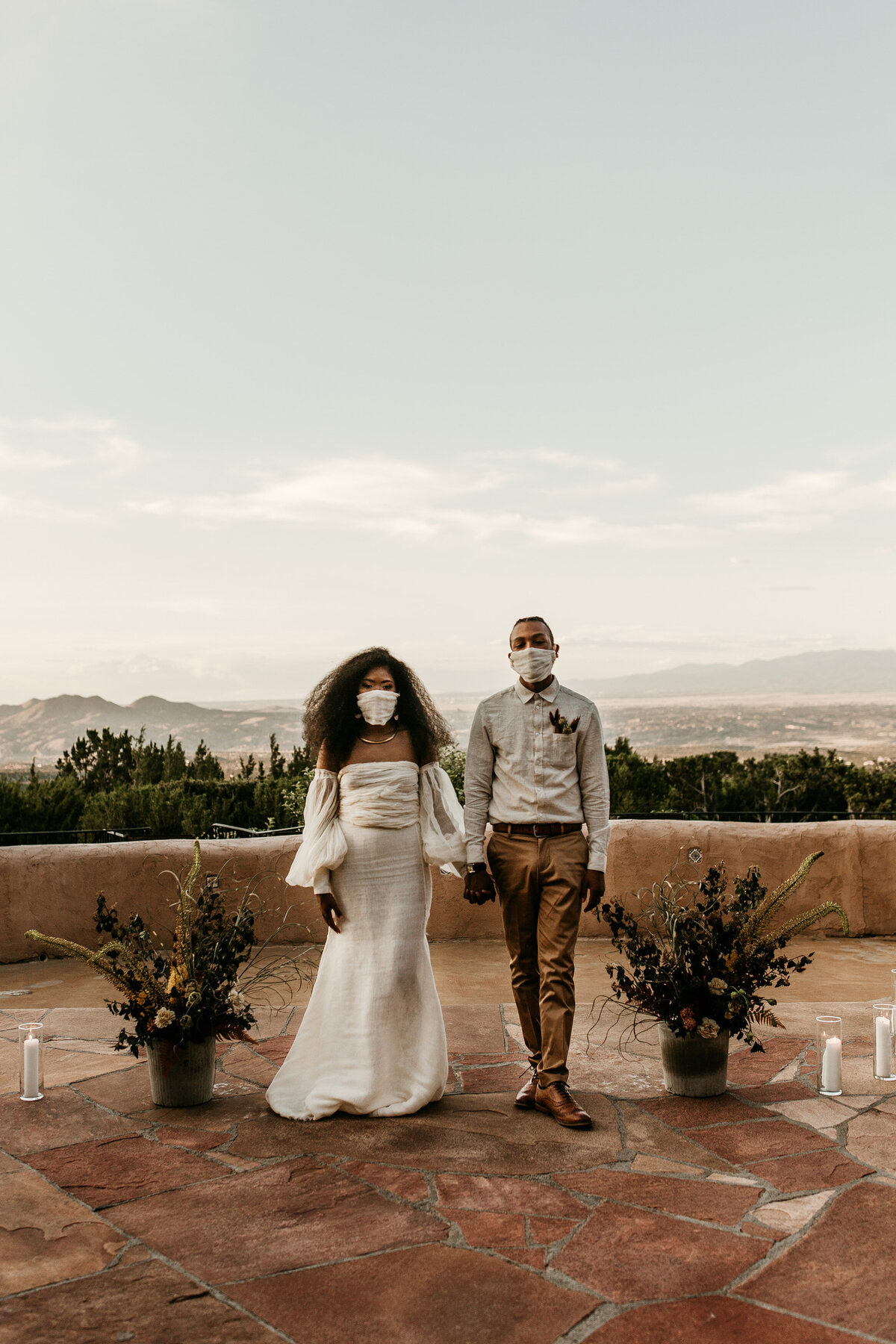 bride and groom holding hands wearing masks at Santa Fe venue courtyard with mountains behind them