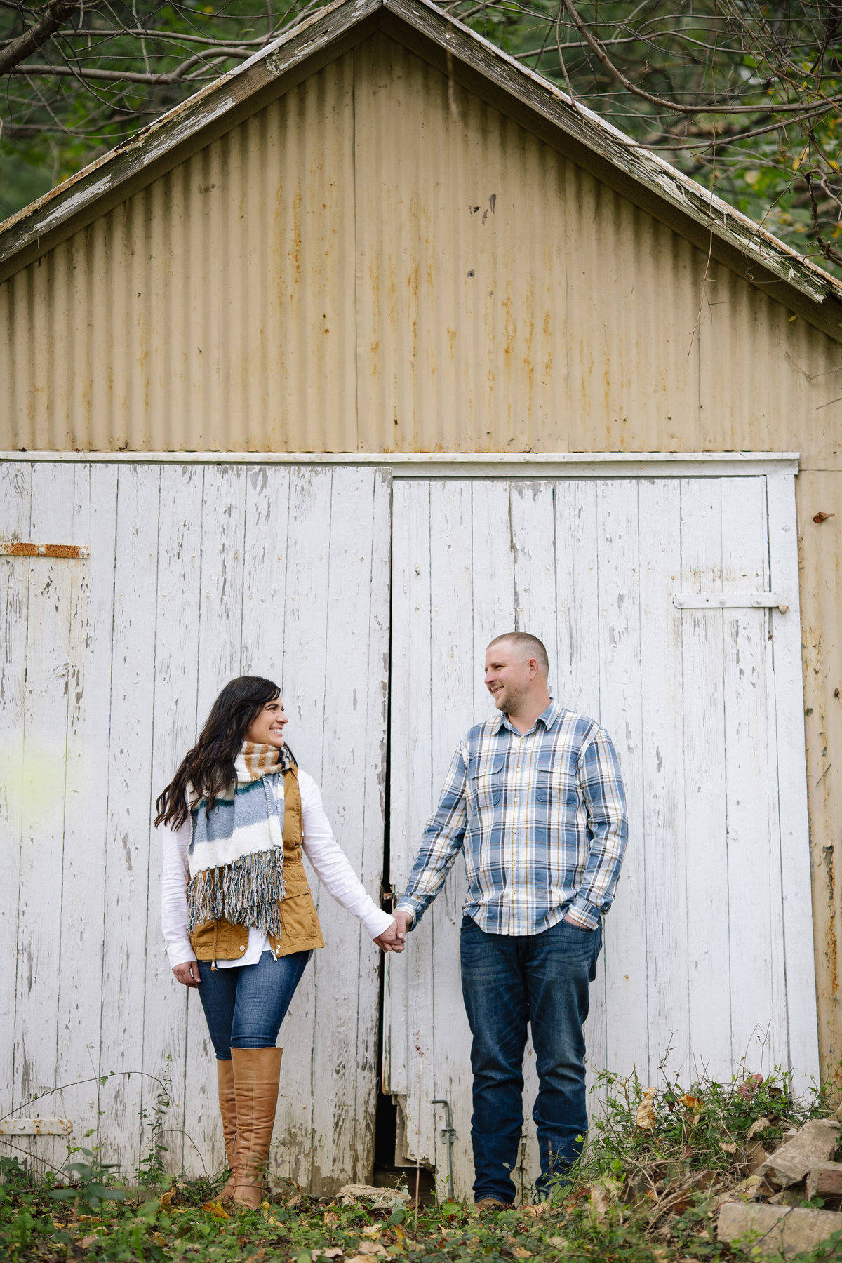engaged couple stand by barn at bayonet farm