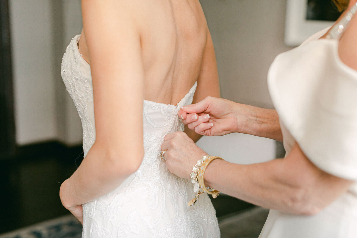 Back of wedding dress being zipped by mother of bride on Dallas Arboretum Wedding