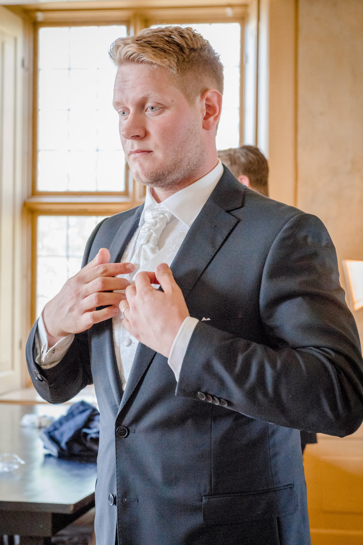 Groom putting on his suit lost in thought