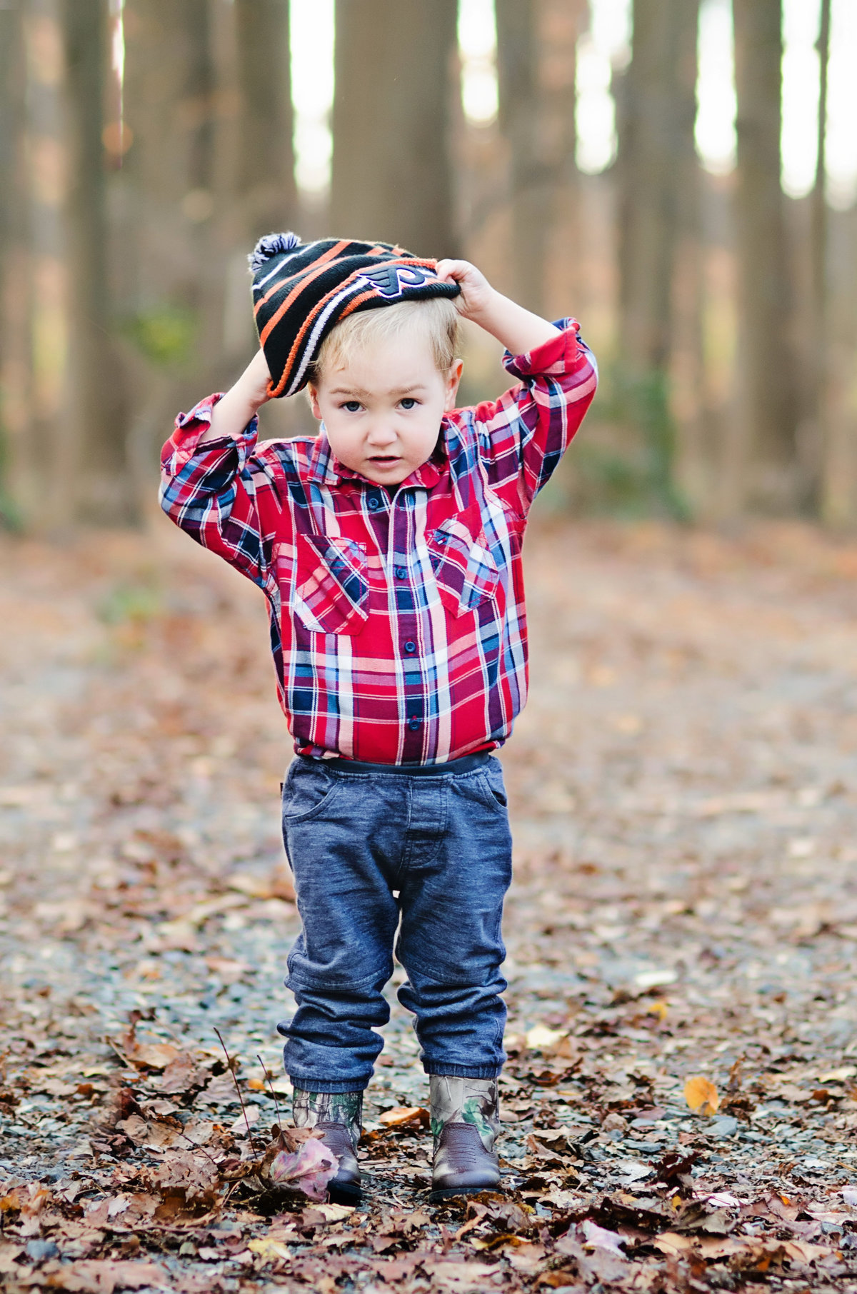 Portrait of a cute toddler putting a hat on during a family session at Nottoway Park in Norther Virginia taken by Sarah Alice Photography