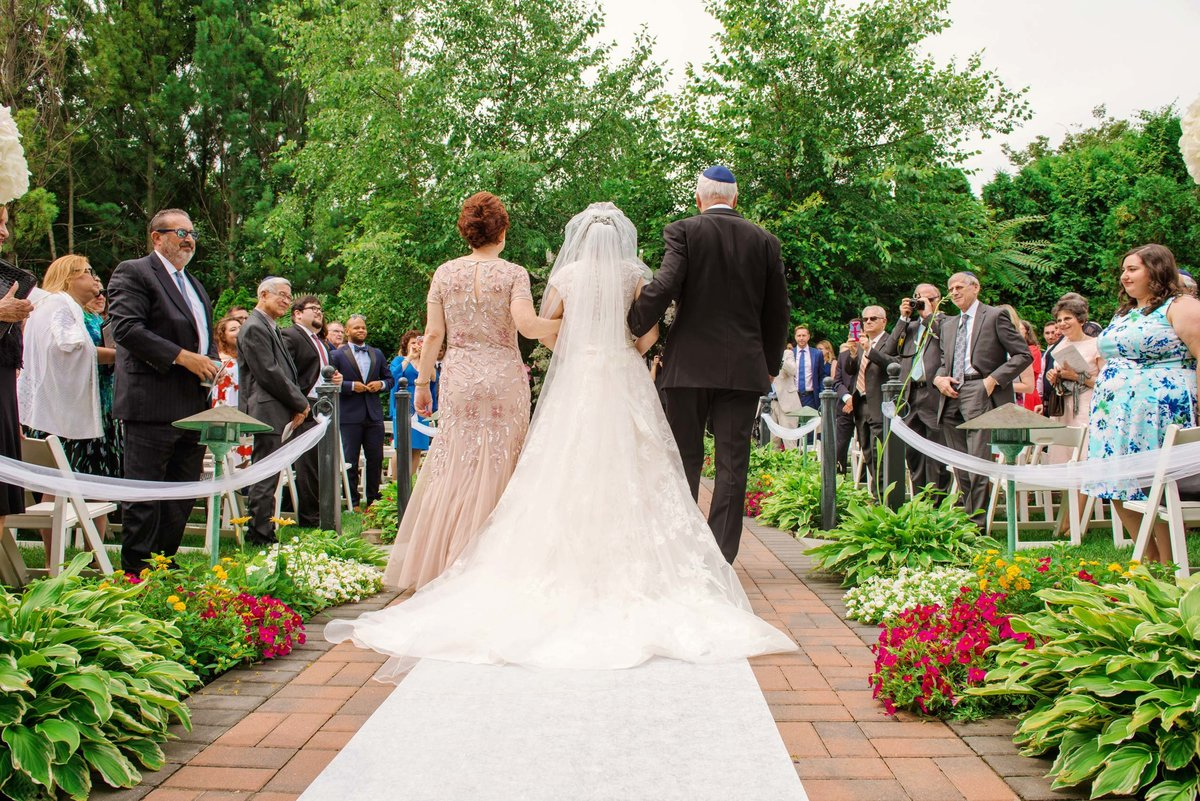Outdoor wedding ceremony, bride walking down the aisle