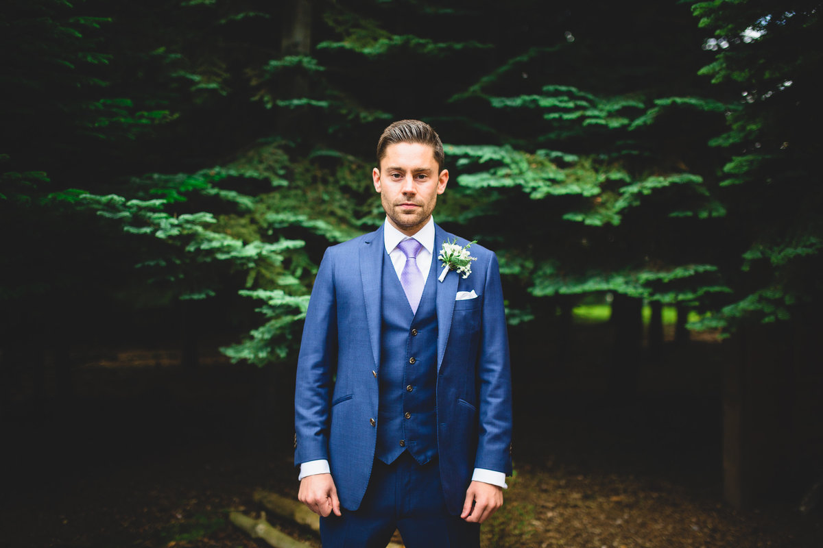 groom wearing blue suit in the woods in front of fir tree