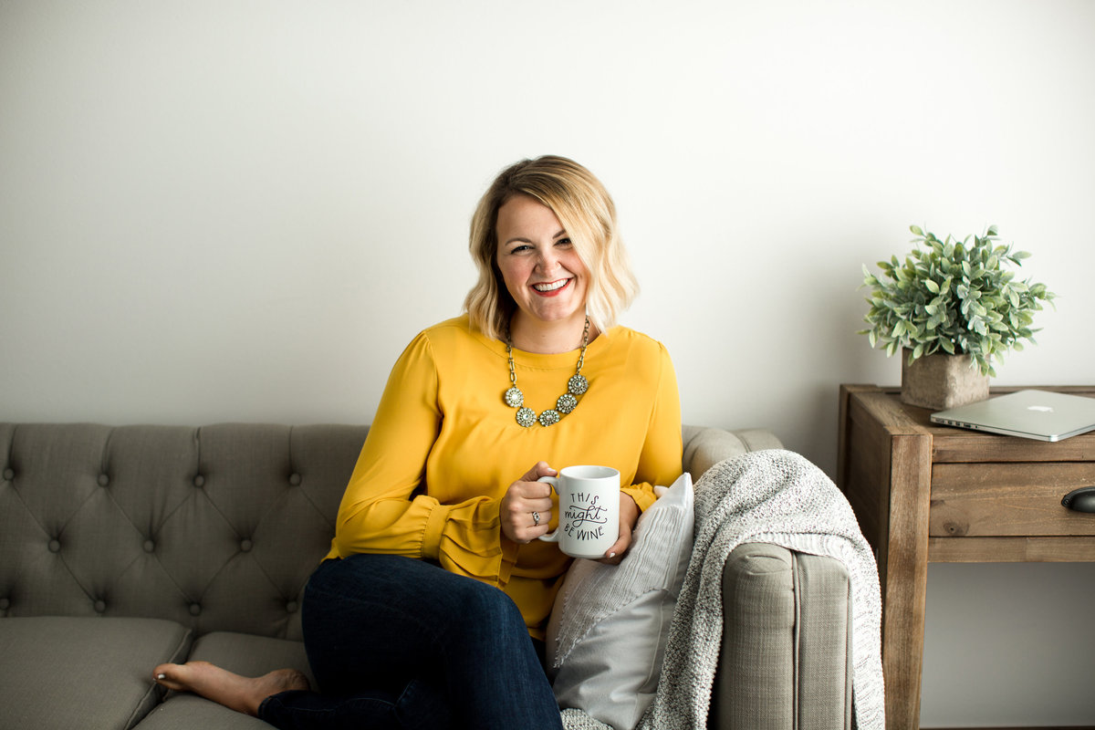 woman in yellow top sitting on couch drinking coffee