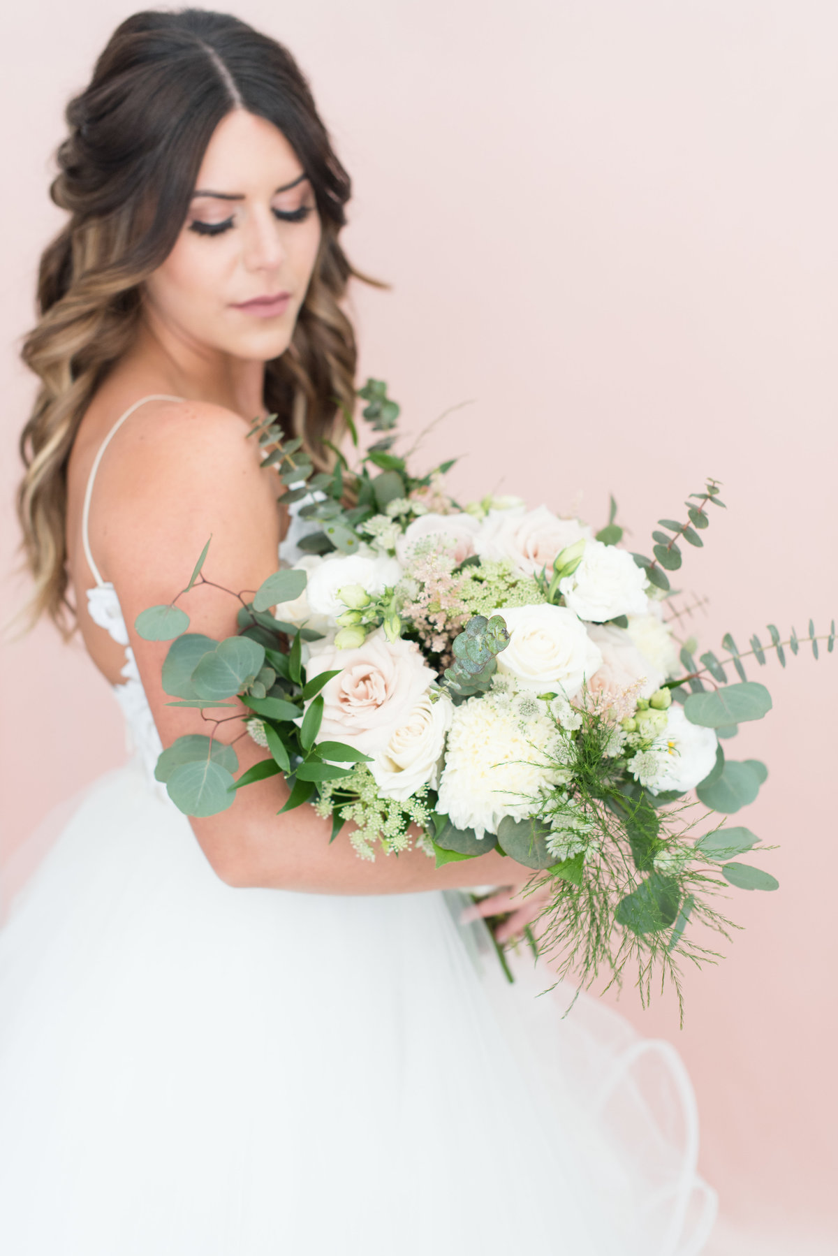 Bride holding her bouquet of quicksand roses and eucalyptus designed by Superior Floral Design in Thunder Bay
