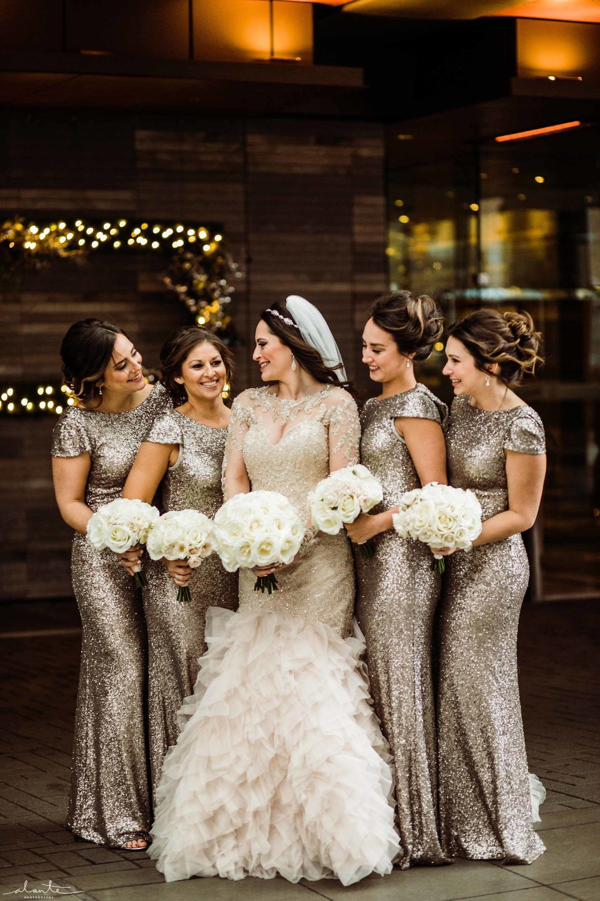 Glamorous bride and her bridesmaids dressed in champagne sequin dresses.