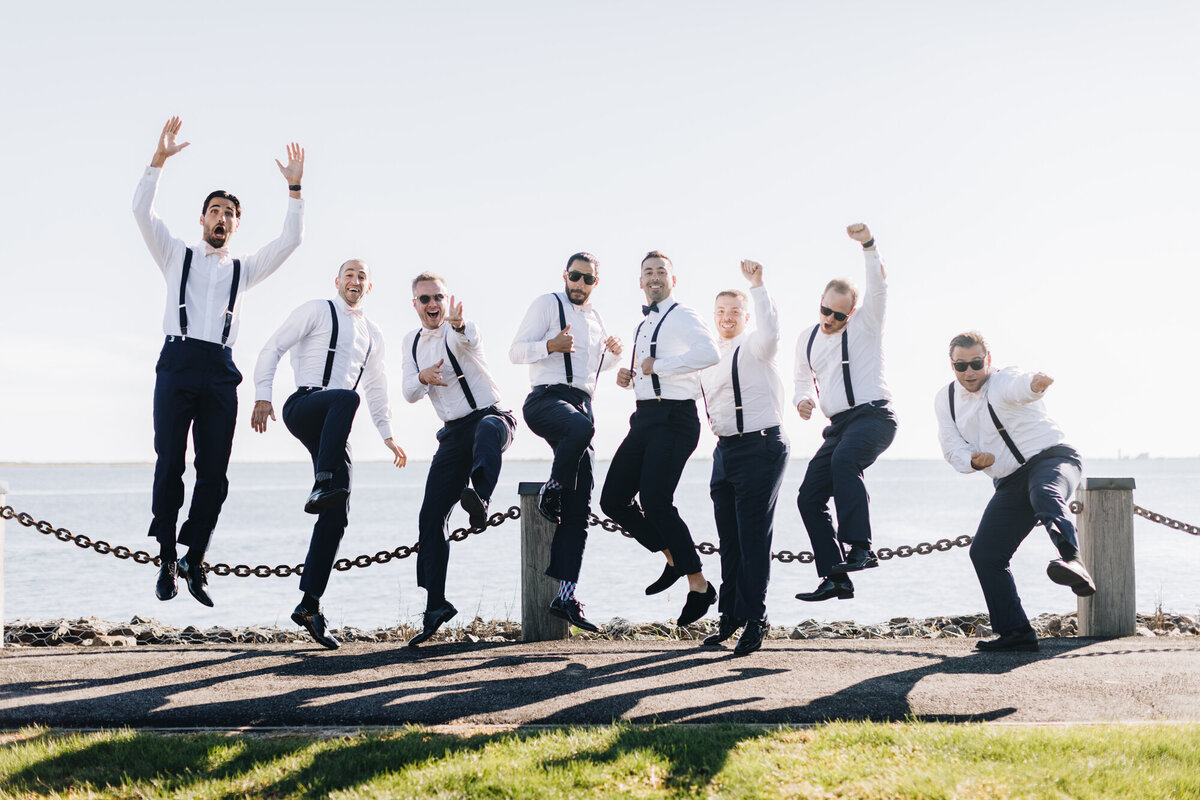 Groomsmen jumping for joy by the water
