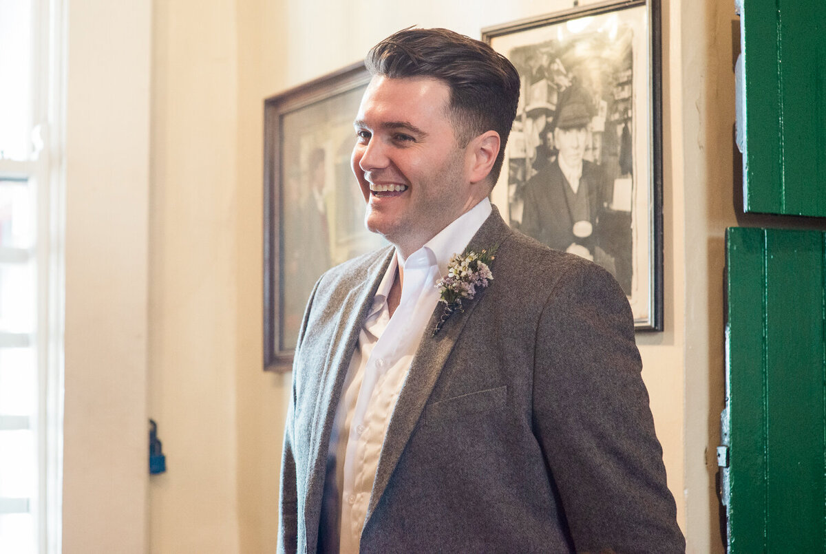 Wedding groom wearing buttonhole, standing in pub laughing
