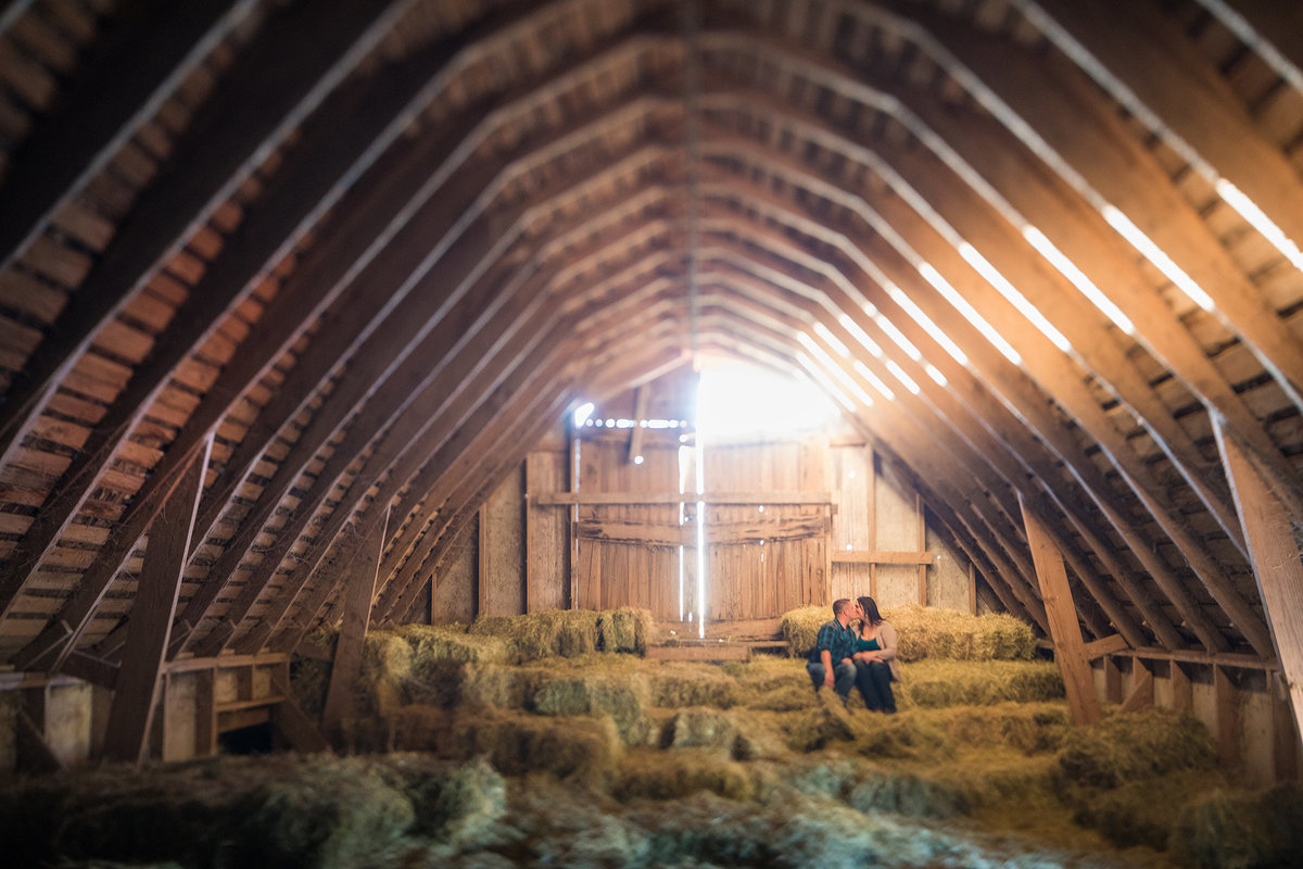couple kissing during their engagement session in the loft of a barn