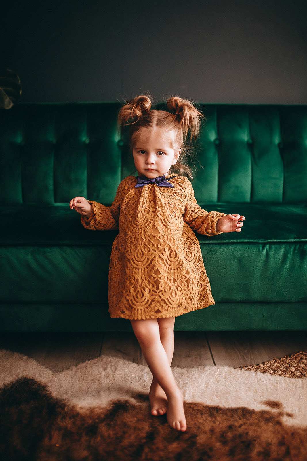 little girl standing next to green couch
