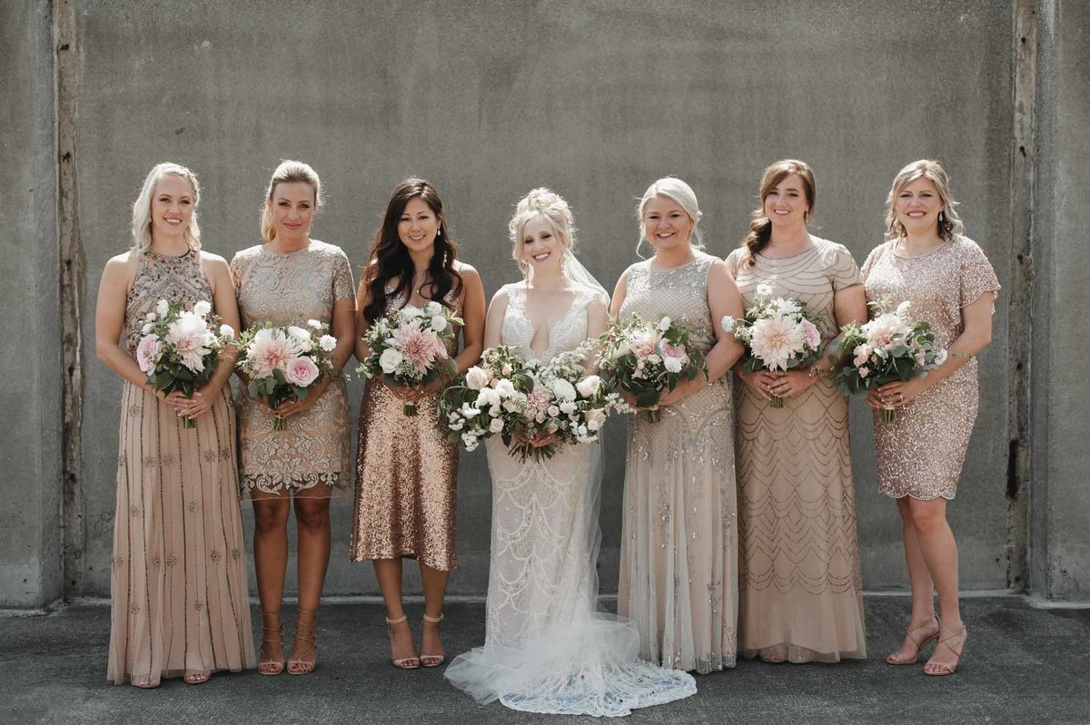 We love the look of bridesmaids all dressed in a unique champagne colored dress and holding cafe au lait dahlia bouquets!