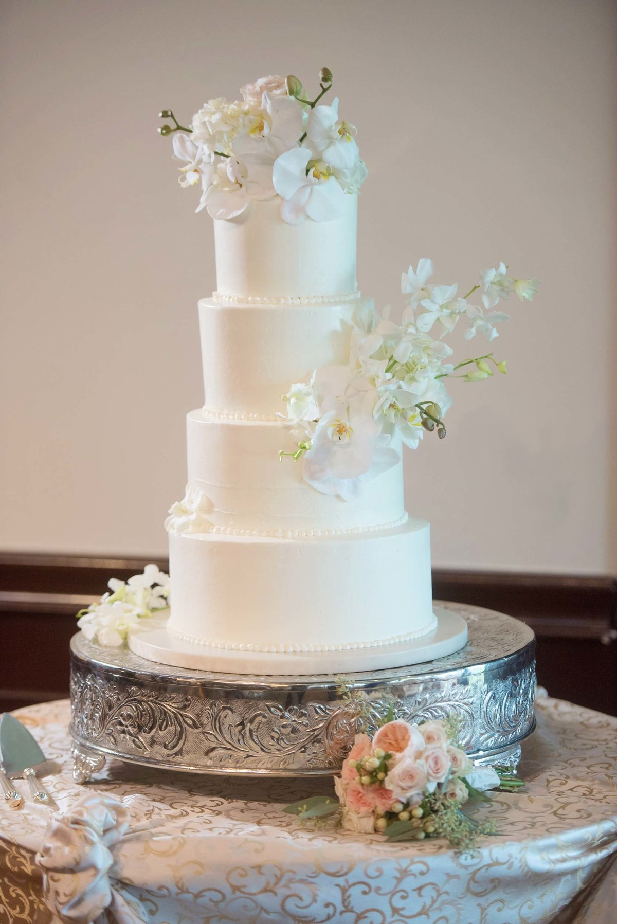 White wedding cake with white flowers at Huntington Crescent Club