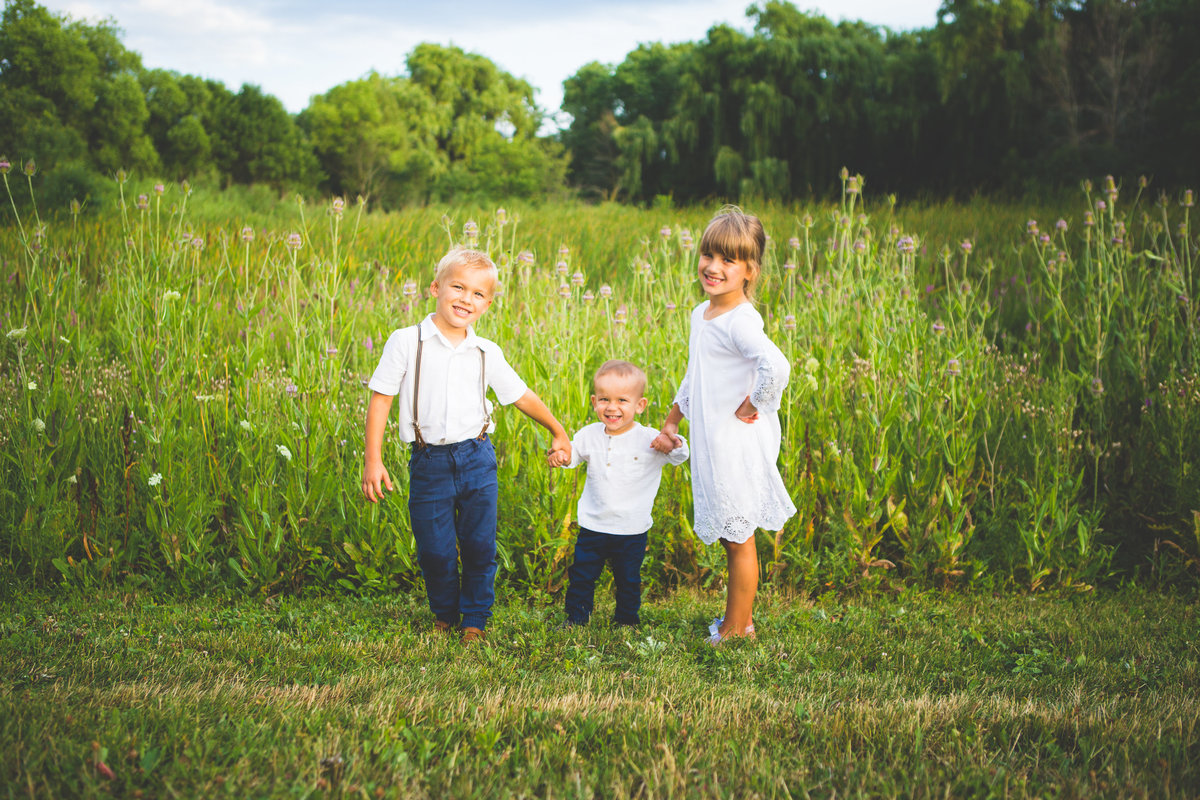 three siblings standing and smiling in field of grass {Burlington Family Photographer}