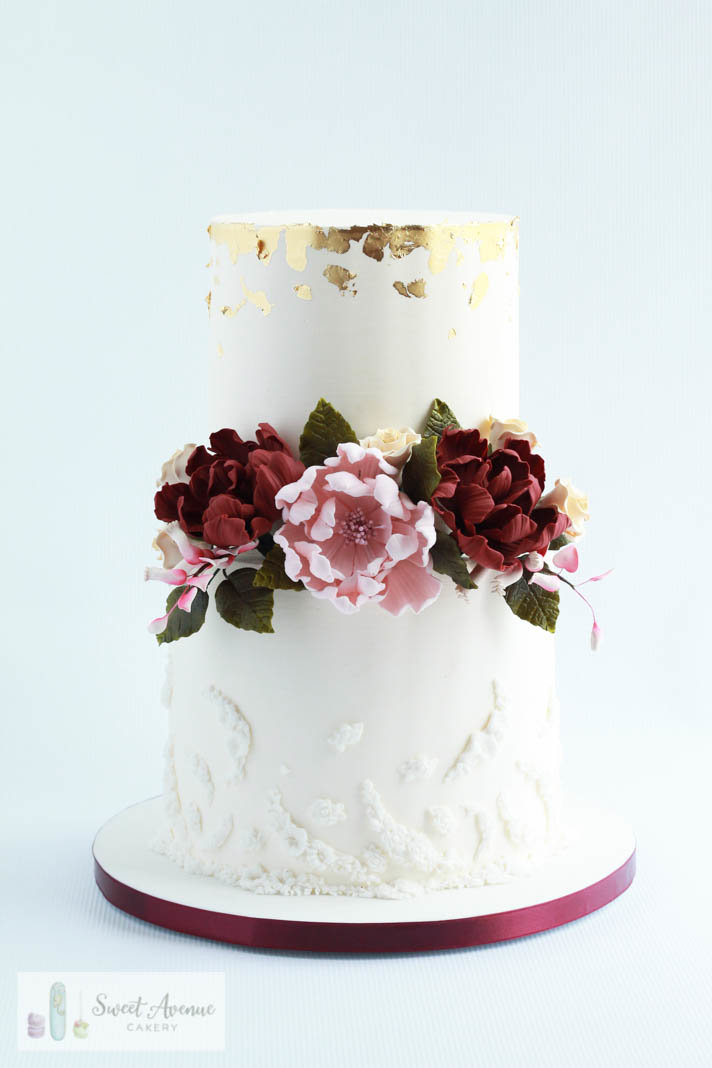white buttercream wedding cake with lace, gold foil and burgundy sugar flowers