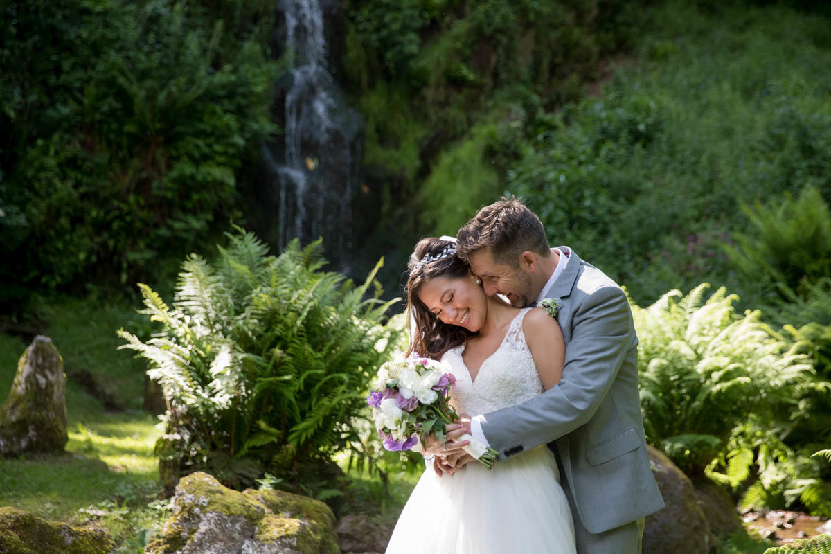 Bride and Groom cuddling by the cascade at Hestercombe Gardens