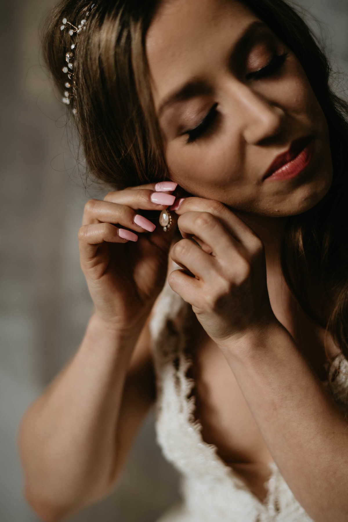 bride putting on her dangling earring set