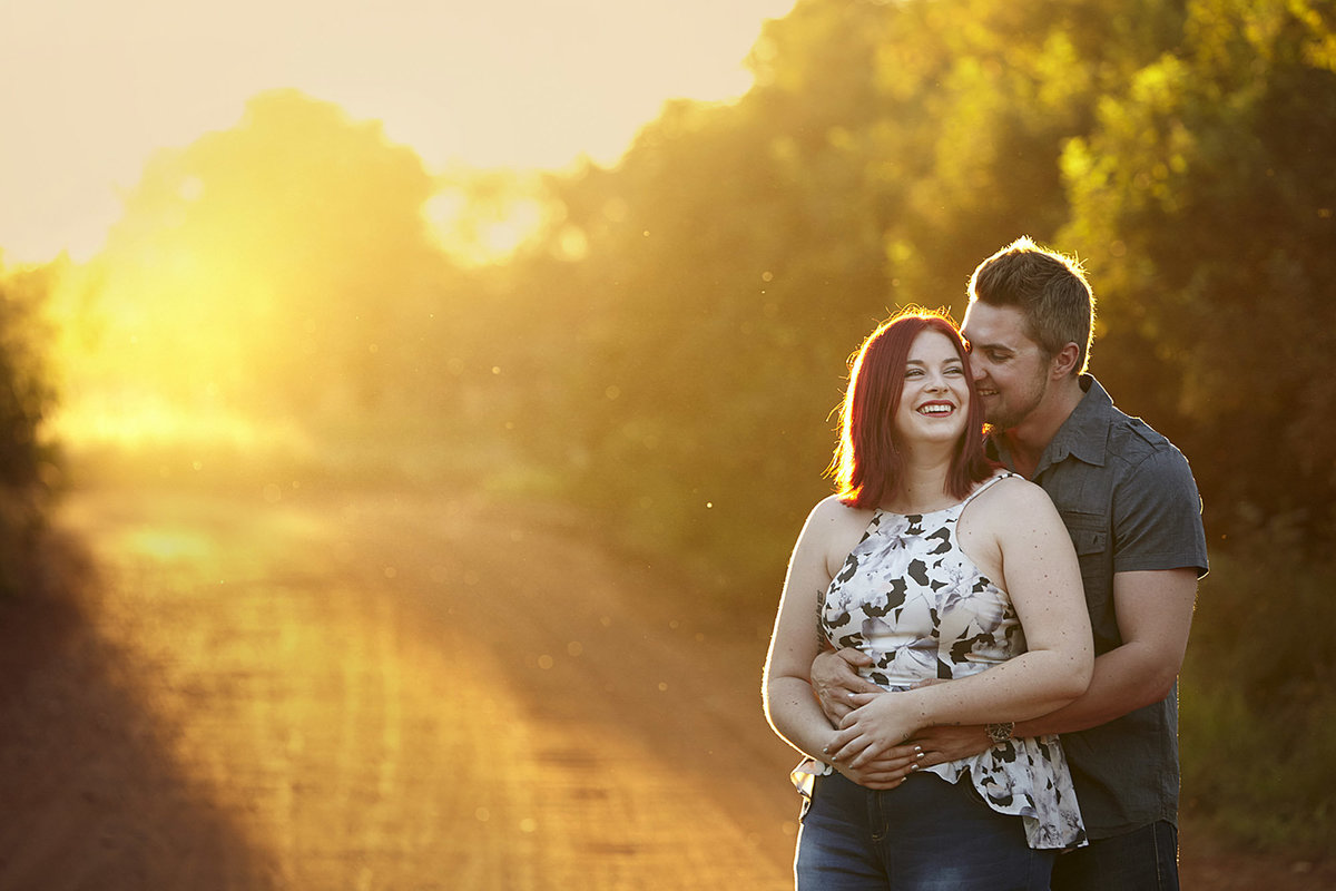 Young couple embracing each other on the right hand side and golden sunlight shining through