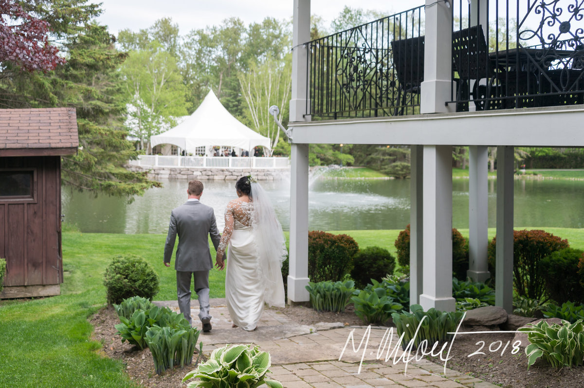 bride and groom walking to their tented reception at Nestleton Waters Inn