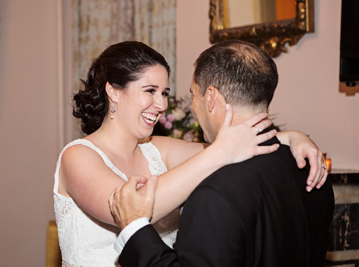 New Orleans destination bride smiles at her groom during wedding reception at The Columns Hotel
