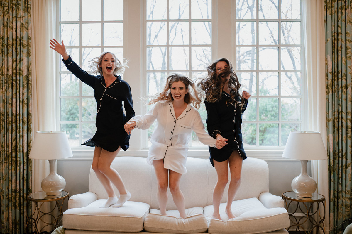 bride and bridesmaids jumping on couch