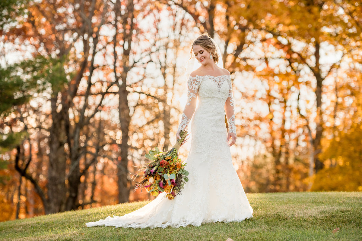 bride with background of autumn leaves during fall wedding and outdoor ceremony