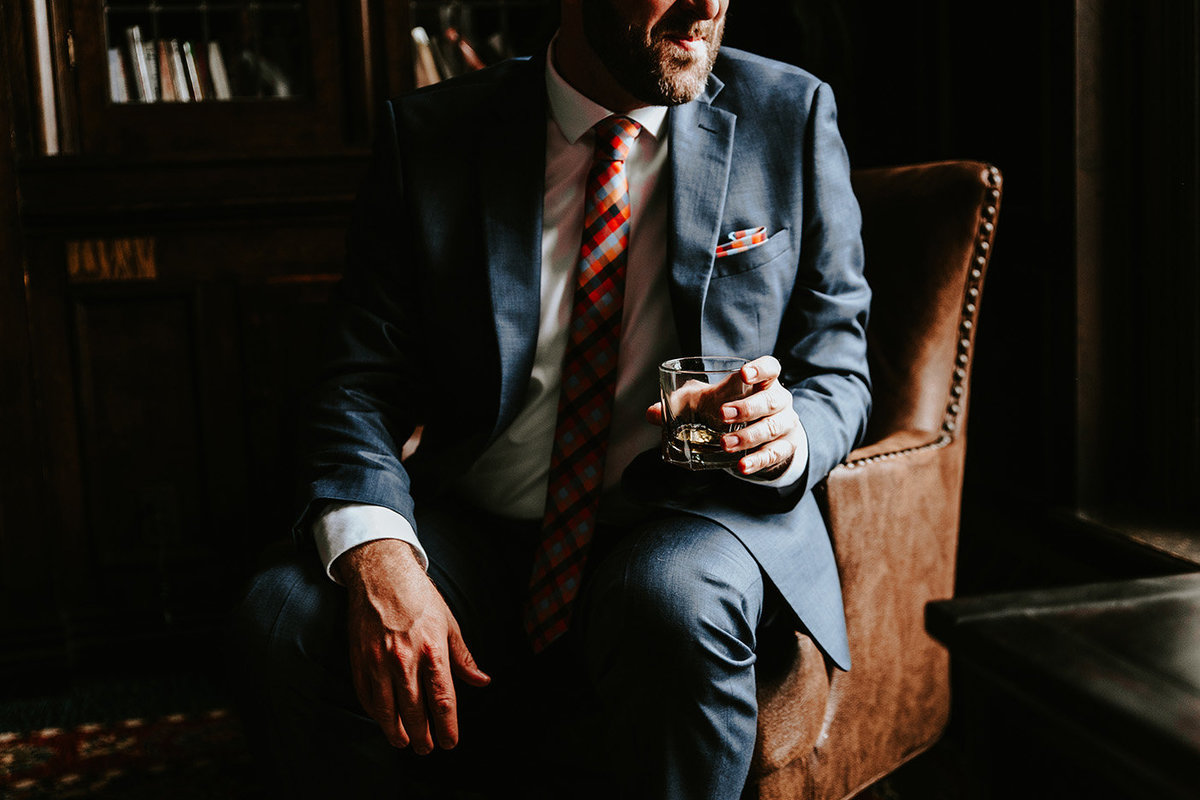 groom holding a rocks glass at the Denver Athletic Club in Denver, CO