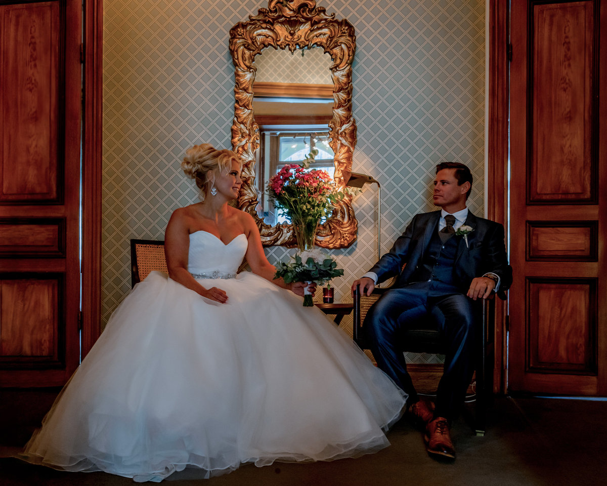 A fall wedding with a wedding couple sitting in a castlelike invoronment indoors, with a mirror between them looking at each other