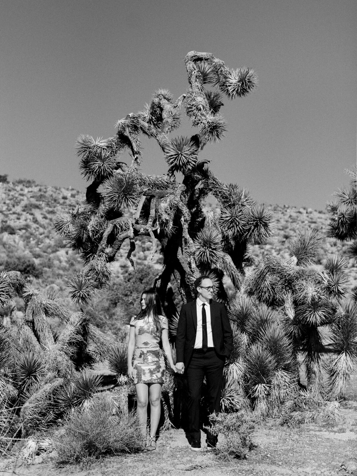 Girl holding hands with man in suit by large Joshua Tree black and white