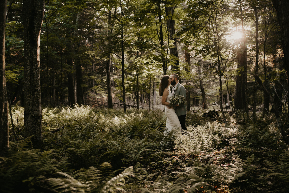 bride and groom kissing in the woods