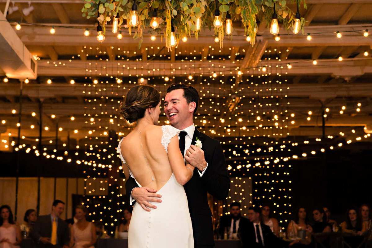 The bride and groom share their first dance under twinkle lights at their Portland Maine wedding