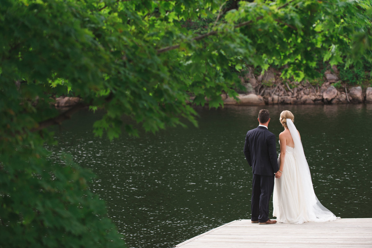 Bride and groom standing on a dock by the lake with long cathedral veil