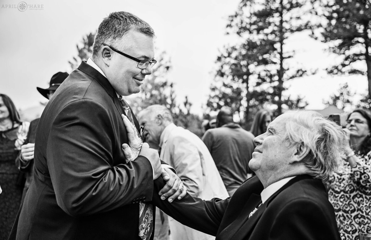 Sweet Moment groom with father in law at a Colorado mountain wedding reception