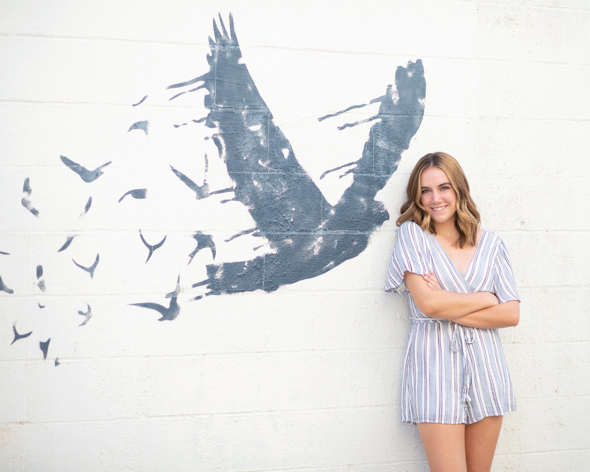 High school senior girl smiles for photo in front of white wall with bird painting