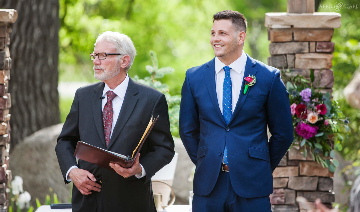 Colorado groom smiles as his bride walks down the aisle at Wedgewood Weddings on Boulder Creek