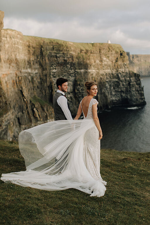 Ireland & US Wedding Planner, bride and groom standing alongside cliffside