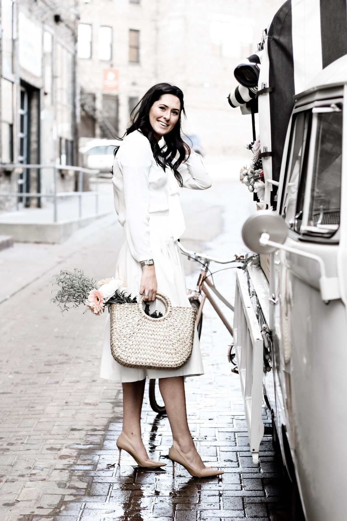 A Paris-esque photo of a woman shopping for flowers with a market bag and bicycle