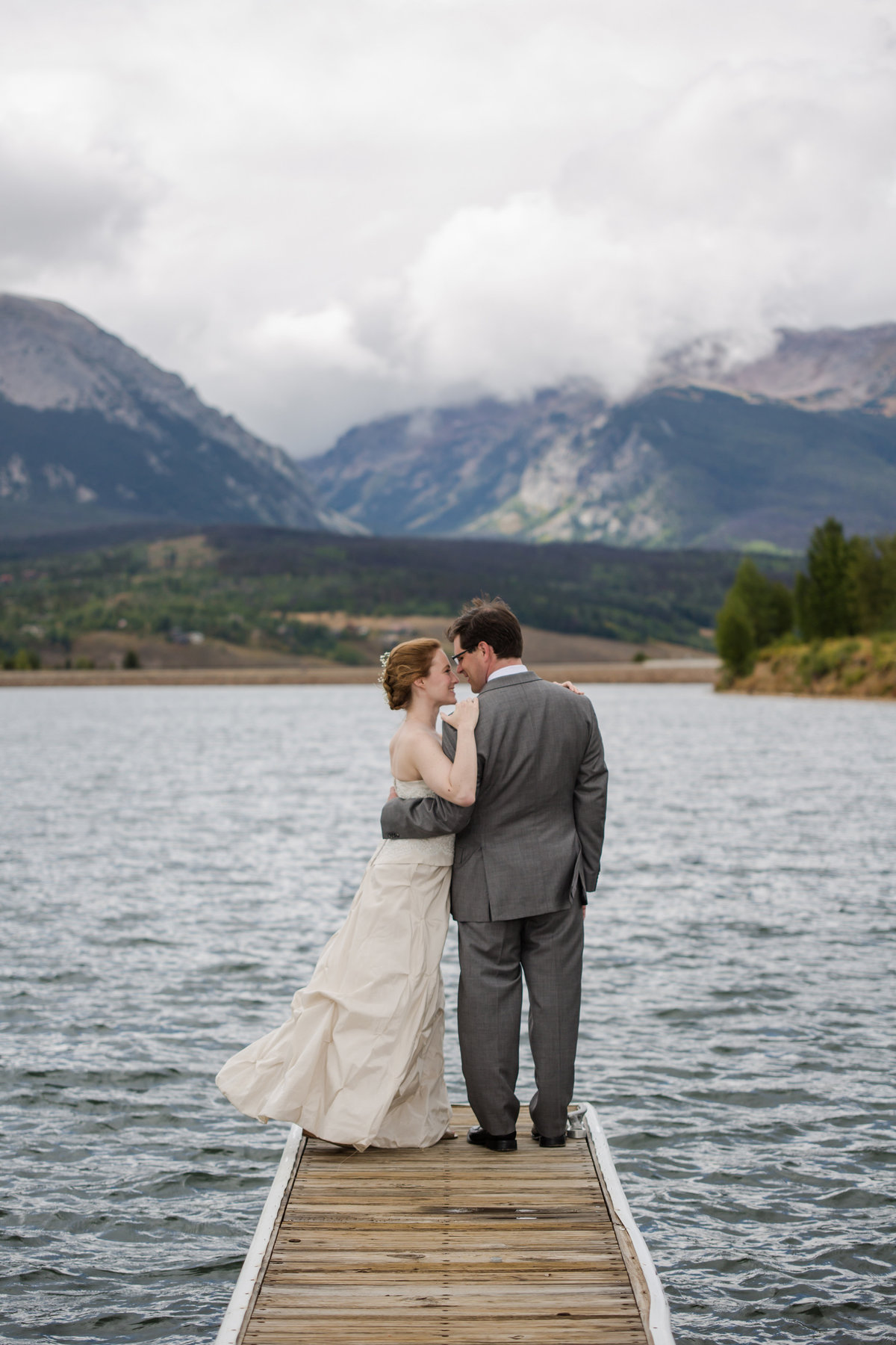couple on dock on lake with mountains