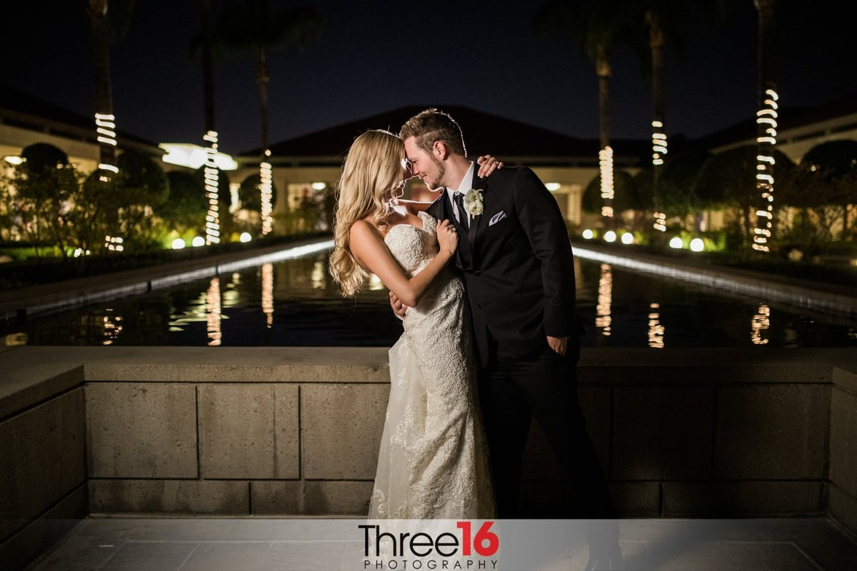 Tender moment at night between the Bride and Groom in front of the reflecting pool at the Richard Nixon Library